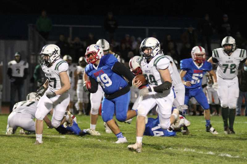 PMG PHOTO: ANDY DIECKHOFF - Estacada senior Jake Behrman runs for the first of his three touchdowns on Thursday night against Madras.