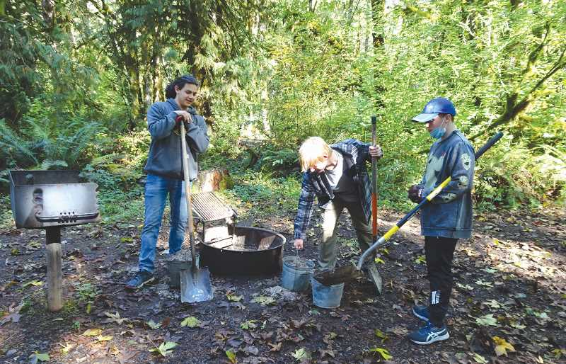 COURTESY PHOTO: ASAKO YAMAMURO - Members of Canby Scout Troop 82 clean the ash out of the campfire rings along the Molalla River Corridor.