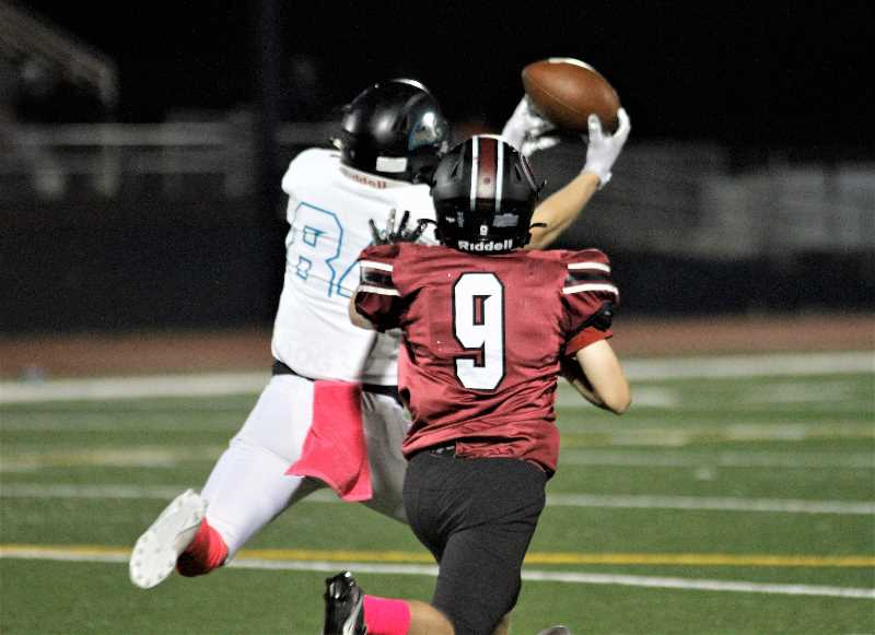 PMG PHOTO: WADE EVANSON - Century receiver Kyle Hamnes makes a streaking catch prior to going 95 yards for a touchdown during the Jaguars' game with Glencoe Thursday night, Oct. 7, at Hare Field in Hillsboro.