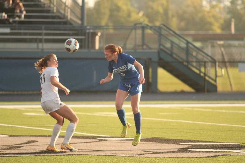 PMG PHOTO: TANNER RUSS - Woodburns Caitlynn Spencer heads the ball away against Sisters.