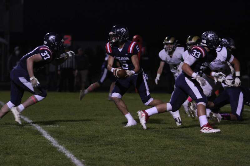 PMG PHOTO: TANNER RUSS - Kennedy quarterback Riley Cantu hands the ball off to William Schaecher, a familiar sight in a run heavy 34-14 win over Regis on Friday, Oct. 8.