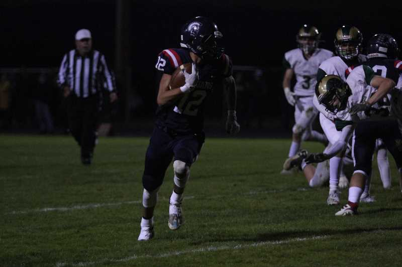 PMG PHOTO: TANNER RUSS - Kennedys Elijah Traeger takes off downfield against Regis in the Trojans homecoming game. Kennedy defeated Regis 34-14.