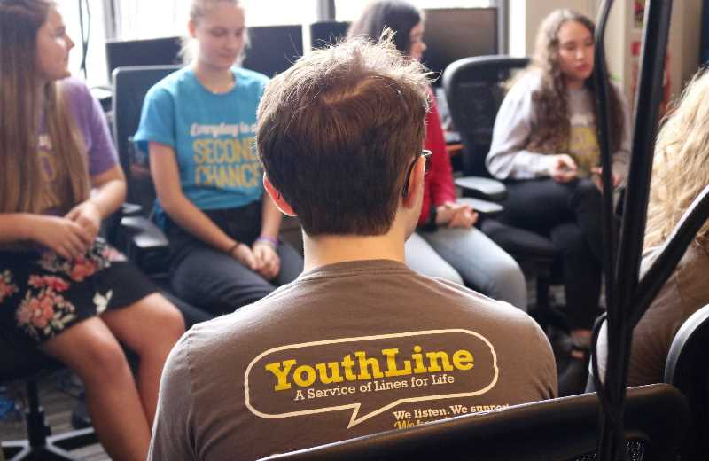 PMG PHOTO: ZANE SPARLING - Student volunteers at YouthLine share their experiences helping peers with mental health issues at the Lines for Life office in 2019.
