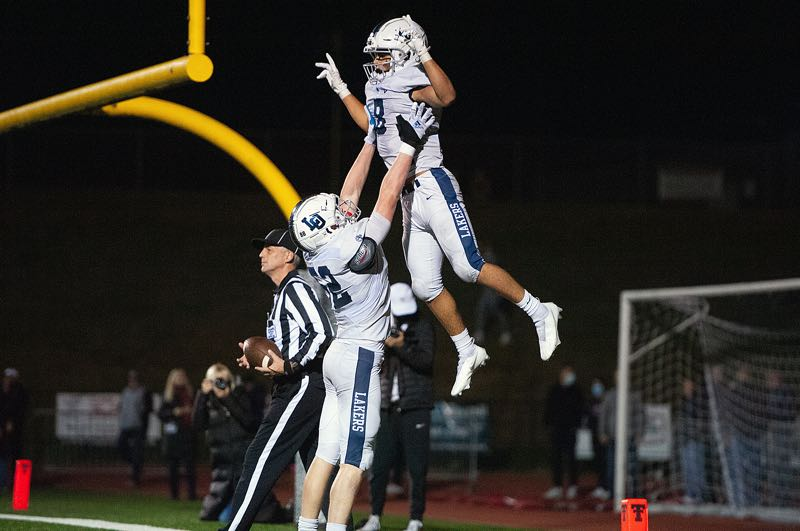 PMG PHOTO: JOHN LARIVIERE - Lake Oswego senior Gabe Olvera gets lifted into the air after scoring one of his two rushing touchdowns during the Lakers' 35-26 win over Tualatin at Tualatin High School on Friday, Oct. 8.