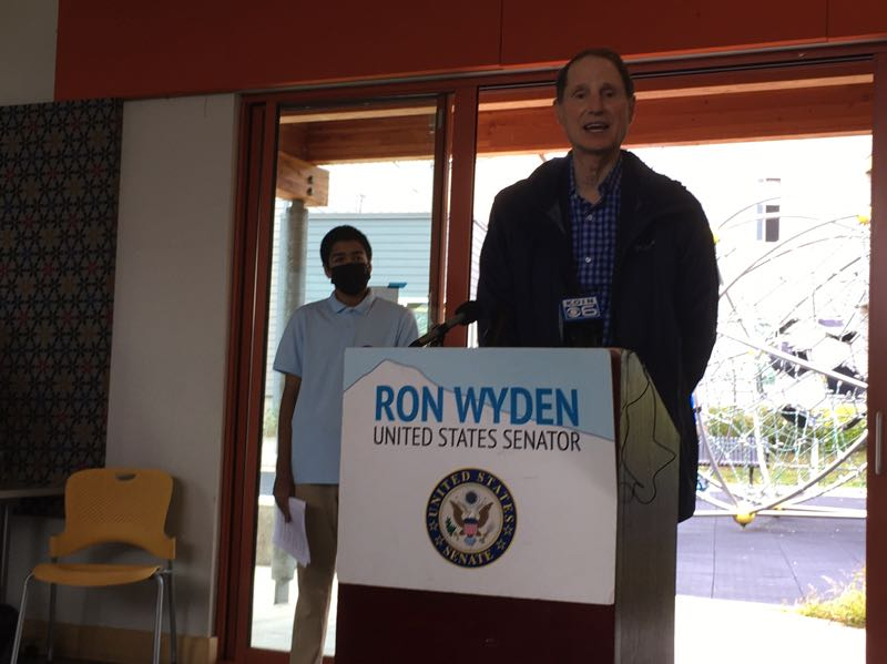 PMG PHOTO: PETER WONG - U.S. Sen. Ron Wyden, D-Ore., opens an event Friday, Oct. 2, in Southwest Portland with some of the advocates for social supports and climate action proposed in President Joe Biden's Build Back Better budget pending in Congress. Behind Wyden is Yusuf Arifin, a junior at Sunset High School who spoke for federal tax breaks Wyden has proposed to promote alternative power sources and energy efficiency.