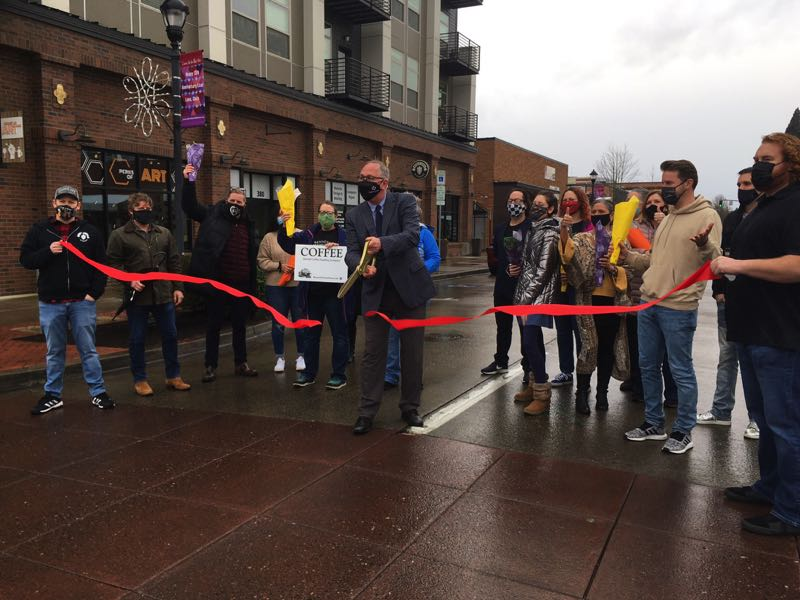PMG PHOTO: MAX EGENER - Hillsboro Mayor Steve Callaway celebrates eased COVID-19 restrictions on businesses by cutting a ribbon at a 'grand reopening' of downtown at East Main Street in March.