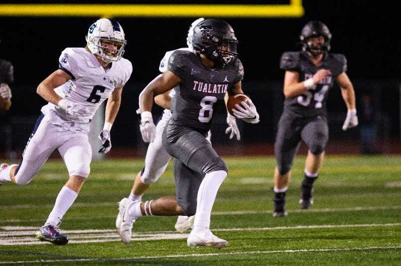 PMG PHOTO: JOHN LARIVIERE - Tualatin's Malik Ross runs the ball during the Timberwolves' loss to Lake Oswego last Friday, Oct. 8, at Tualatin High School. The Lakers sit atop the Three Rivers League standings with the 35-26 upset win.