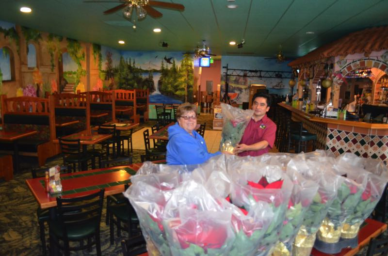 COURTESY PHOTO: SUE HOBART - Dea Gray delivers 30 large poinsettias to Ixtapa Mexican Restaurant in Scappoose in 2019. (The sale was canceled last year due to COVID-19.)