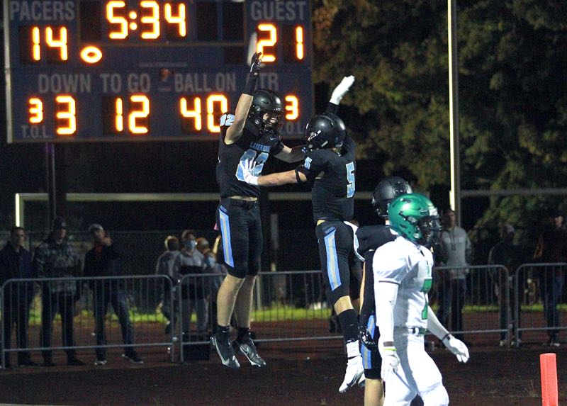 PMG PHOTO: MILES VANCE - Lakeridge sophomore Joey Olsen (left) leaps into the air to celebrate a touchdown in his team's Friday loss to West Linn.