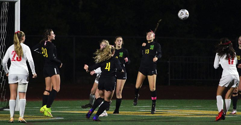 PMG PHOTO: MILES VANCE - West Linn senior Asia Hardin heads away and Oregon City attack during the Lions' 2-1 win at West Linn High School on Wednesday, Oct. 6.