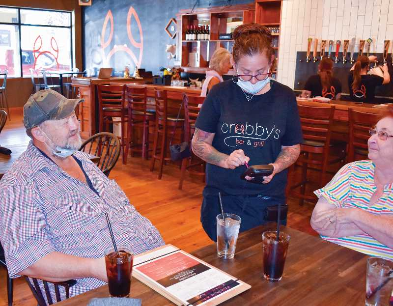 RAMONA MCCALLISTER - Steve and Yvonne Gibson order off the dinner menu at Crabby's Bar and Grill on Wednesday, Oct. 6 during the soft opening of the restaurant. The soft opening was very successful and well-attended, and Crabby's is now open from 11 a.m. to 9 p.m., seven days per week.