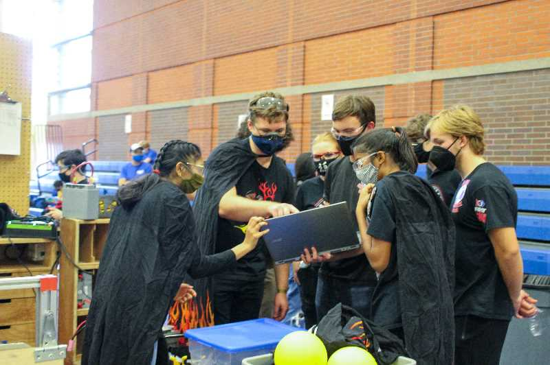 PMG PHOTO: MIA RYDER-MARKS - Between games, the students met in the 'pit' to check over their robots and strategize.