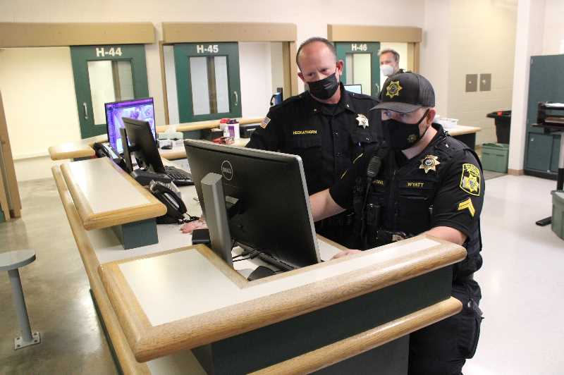 PMG PHOTO: PAT KRUIS  - Sheriff Marc Heckathorn confers with Cpl. James Wyatt at the jail intake center.
