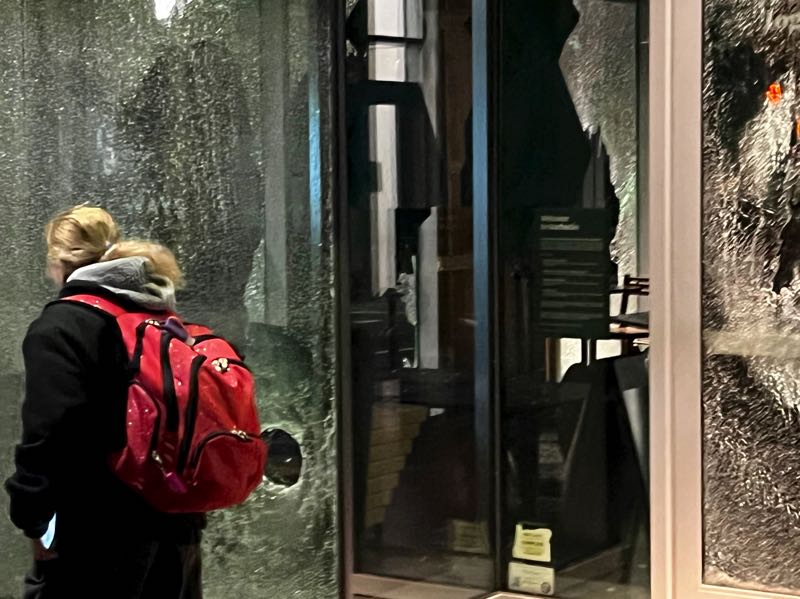 PMG PHOTO: ZANE SPARLING - A woman walks past the shattered storefront of a Starbucks coffee shop near the Multnomah County Justice Center on Oct. 12.