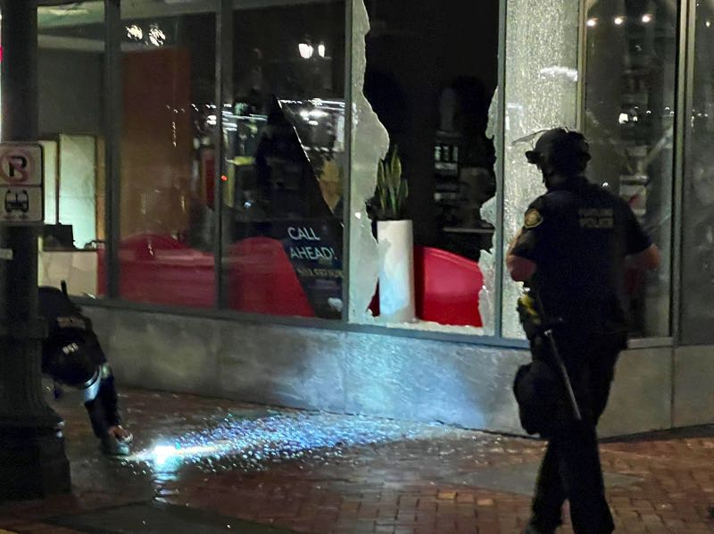 PMG PHOTO: ZANE SPARLING - Police investigate the broken glass of a storefront on 2nd Avenue in downtown Portland on Oct. 12, the two-year anniversary of Sean Kealiher's death.
