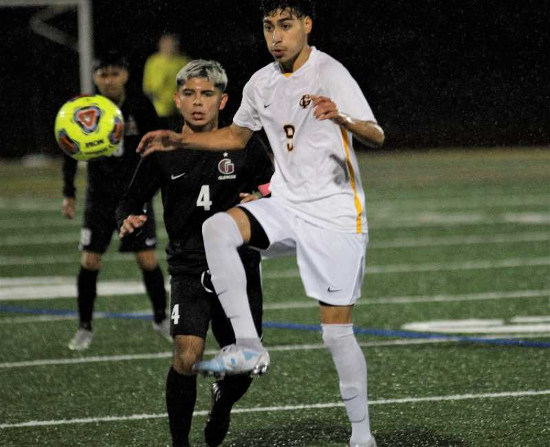 PMG PHOTO: WADE EVANSON - Forest Grove's Bryan Rodriguez and Glencoe's Ivan Alfaro fight for a loose ball during the two teams' game Tuesday night, Oct. 12, at Hare Field in Hillsboro.