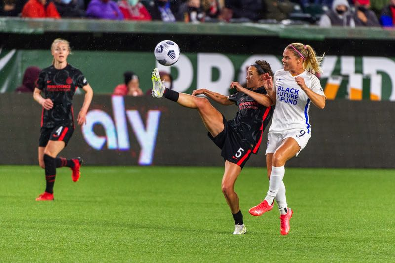PMG PHOTO: DIEGO G. DIAZ - Portland defender Emily Menges clears the ball as OL Reign's Eugenie Le Sommer pursues during Wednesday's National Women's Soccer League match at Providence Park. The game ended a 1-1 draw.