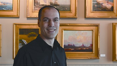 by: RAMONA MCCALLISTER/CENTRAL OREGONIAN - Dennis Jones stands in front of some paintings at Wild River Art Gallery.
