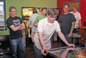 by: Sarah Toor, As other members look on, Kyle Poquette battles the Creature from the Black Lagoon during a Portland Pinball League match at Billy Ray's Neighborhood Dive.