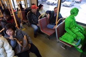 by: L.E. BASKOW, Being green in Portland isn't all that unusual, as street performer Wells Oviatt finds out riding MAX to work downtown.