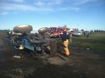by: TODD GARY - Firefighters check damage to a tractor on Barlow Road after a collision with a car Friday.