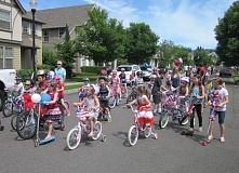 by: TIMES PHOTO: BARBARA SHERMAN - Kids on all types of vehicles get to ride safely in the streets of King City's Edgewater on the Tualatin subdivision during the annual Fourth of July parade, which this year attracted at least 400 participants.