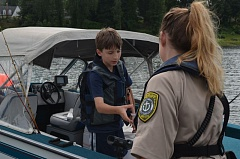 by: SUBMITTED PHOTO - A deputy gives a young boater a candy voucher as a reward for wearing a life jacket while on the Clackamas River.