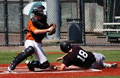 by: DAN BROOD - PLAY AT THE PLATE -- Tigard catcher Sam Nihill (left) holds up the ball after tagging out Sherwood's Cam DuFault during Tuesday's OIBA game played at Tigard High School. The Longhorns came away with a 3-2 win over Sherwood.