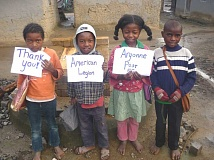 by: SUBMITTED PHOTO - In the town of Ambonidray, Madagascar, where Kara Leavitt served, she helped the townspeople build five wells, which were funded in part by the Sons of the American Legion at Sherwood Argonne Post 56, and here some grateful kids hold up a thank you sign.