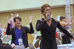 by: COLLEEN CAHILL STUDIOS - LaKeisha Michelle, singer/songwriter/entertainer, inspires the room to stand up and clap along to her song at the 2014 Oregon Womens Conference.