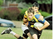 by: SETH GORDON - Busting loose - Recent Newberg graduate Spencer Bain shrugs off a Pendleton defender during a        summer rugby sevens game July 19 at Northgate Park in Portland.