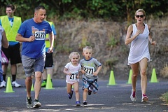 by: TIMES PHOTOS: JOHN LARIVIERE - The Jones family of Jerry, 3-year-old Ruby, 5-year-old JJ and Mary race toward the finish line of the Party in the Park Family Triathlon on Saturday morning.