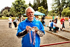 by: DAVID F. ASHTON - Portland Petanque Club President Steve Walker shows off some of the many trophies from FPUSA to be awarded during the competition.