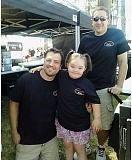 Photo Credit: MARIANNE KNAPP - Nagging Wife BBQ won the people's choice award at the WildRiver BBQ Cook-off competition. They were one of the sponsors of the BBQ and Bingo night for Brooke Garbart last December, and they finally got the chance to meet this special little girl at the competition. Pictured with Brooke at their booth in the WildRiver BBQ Cook-off are Robert Knoke, left and Ben Fullerton, both of Nagging Wife BBQ.