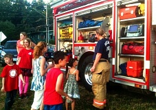 Photo Credit: PHOTO COURTESY OF CITY OF PORTLAND CRIME PREVENTION PROGRAM VIA FACEBOOK - Kids interacted with a Portland firefighter at the 2013 Crestwood neighborhood National Night Out.