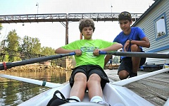 Photo Credit: TIDINGS PHOTO: VERN UYETAKE - Varsity rower Logan Rower, right, helps novice Joe Sandmier get situated in a boat.