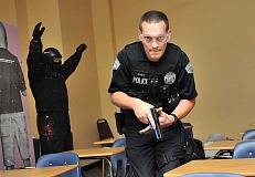Photo Credit: REVIEW PHOTO: VERN UYETAKE - Officer Jacob Jones maneuvers through a classroom during an active threat training exercise last week at Lake Oswego High School.