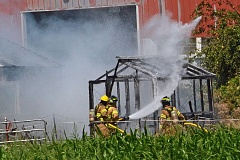 Photo Credit: JOHN HOWARD - Firefighters from Scappoose Fire District extinguish flames from a small greenhouse at a property on Johnson's Landing Road Monday afternoon. The fire destroyed the greenhouse, but the main structure was not damaged.