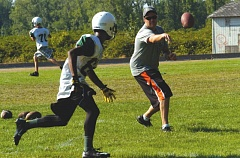 Photo Credit: ESTACADA NEWS: PARKER LEE - Rangers football coach Andy Mott takes running backs through drills during Mondays opening practice session.