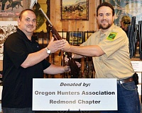 Photo Credit: SUBMITTED PHOTO - Canby's Matt Bauder (left) is awarded his new Savage .17 HMR rifle. His name was drawn from a pool of hunters who filled out daily Access and Habitat Program permits.