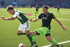 Photo Credit: TRIBUNE PHOTO: JAIME VALDEZ - Seattle Sounders defender Zach Scott (right) and Portland Timbers midfielder Maximiliano Urruti fight for possession at Providence Park during Sundays MLS game. Seattle won 4-2.
