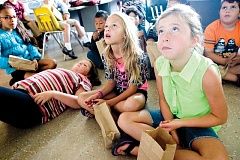Photo Credit: KEVIN SPERL - Gabby Wood, right, and Jaz Petty, center, are deeply focused while enjoying a movie and some popcorn on the last day of the Kiwanis Summer School at Cecil Sly on Thursday, Aug. 14. Haley Nelson, on her back, takes a more relaxed stance.