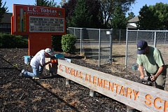 Photo Credit: HILLSBORO TRIBUNE PHOTOS: DOUG BURKHARDT - Bill Ellis and Bill McSpadden from Harvest Community Church spruce up the Tobias Elementary School sign while participating in a Saturday morning work party at the school.