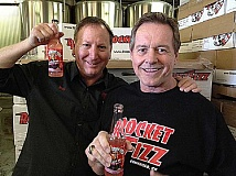 Roddy Piper, right, poses with Rocket Fizz co-founder Robert Poweel and bottles of the 'All Out of Bubble Gum' soda. Piper will be at Progress Ridge on Saturday signing bottles of the soft drink.