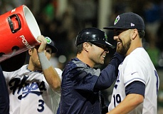 Photo Credit: HILLSBORO TRIBUNE PHOTO: CHASE ALLGOOD - Hops Manager J.R. House celebrates with pitcher Felipe Perez as outfielder Stewart Ijames readies a bucket of sports drink to douse House.