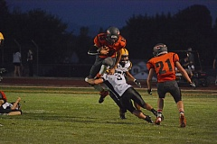 Photo Credit: JOHN WILLIAM HOWARD - Scappoose senior quarterback Joey Krupsky hurdles Cascade cornerback Hunter Thomas late in the second quarter of the Indians' 54-30 victory over the visiting Cougars. Krupsky scored six touchdowns in the game, four with his feet and a pair through the air.