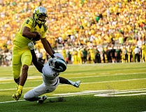 Photo Credit: COURTESY OF DAVID BLAIR - Marcus Mariota, University of Oregon quarterback, wards off a Michigan State defender during Saturday's 46-27 Ducks victory over the Spartans at Autzen Stadium
