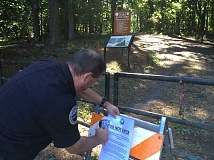 Photo Credit: SUBMITTED PHOTO - Lake Oswego Fire Marshal Gert Zoutendijk posts a closure notice Thursday at a trailhead leading into Cooks Butte Park. The park will remain closed through the weekend.