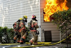 Photo Credit: OUTLOOK PHOTO: TROY WAYRYNEN - Gresham firefighters walk by an apartment engulfed in flames as they battled the two-alarm blaze Monday, Sept. 15, at Golfside Apartments, 1999 N.E. Division St.