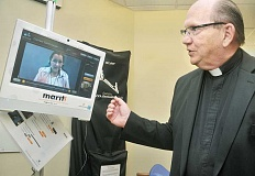 Photo Credit: GARY ALLEN - New techology - Father Tim Bushy, chaplain at Providence Newberg Medical Center, demonstrates ­MARTTI, the facility's new online interpretative service.